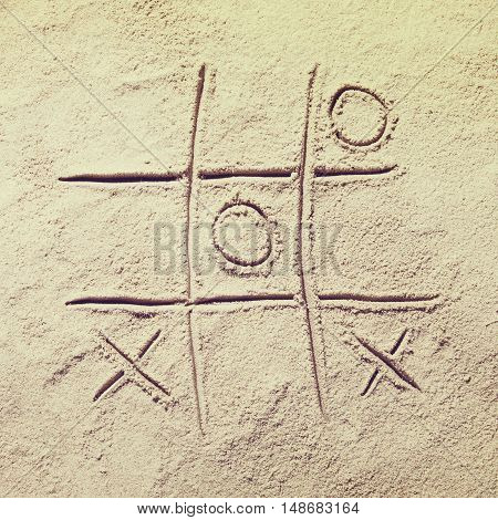 Top view of sandy beach with tic tac toe