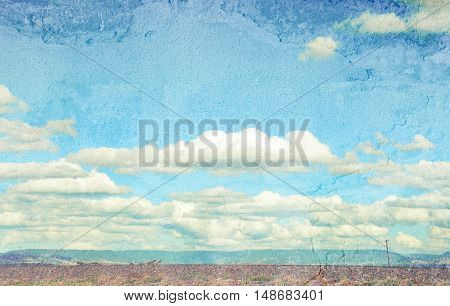 Rural cloudscape with flat road and power lines in foreground and mountain range in background. Faded and textured image with copy space.