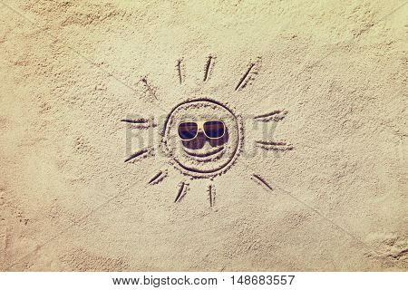 Top view of sandy beach with smiling family faces and sunglasses