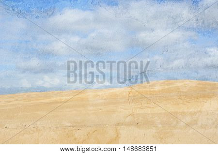 Deserted sand dune under blue cloud filled sky. Grunge, aged, textured image.