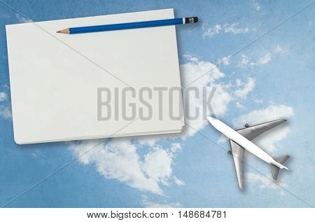 Blank notebook page with plan sky travel background
