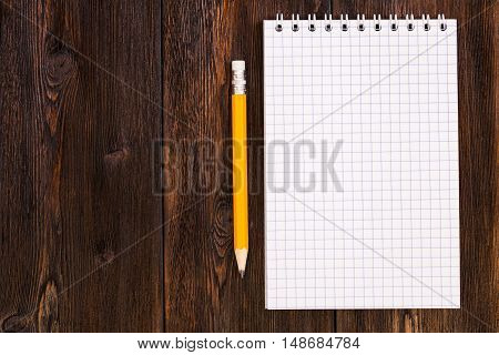 Blank notebook and pencil on a dark wooden background