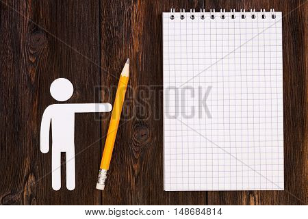 Paper man with pencil and blank notebook, wooden background. Abstract conceptual image