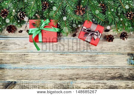 Christmas or New Year background with gift box, fir branch and conifer cone on wooden rustic board, festive snow effect. Top view, flat lay.