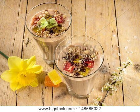 Chocolate pudding with walnuts and marmalade decorated with flowering daffodils on a wooden background. Healthy eating.