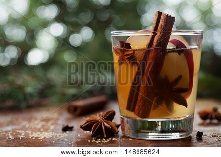 Christmas mulled apple cider with spices cinnamon, cloves, anise and honey on rustic table. Traditional drink on winter holiday, selective focus.