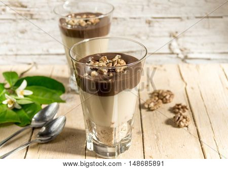 Chocolate Vanilla pudding with walnuts in a glass on a wooden background