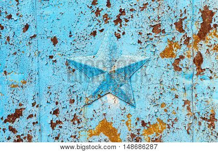 Blue peeling paint and star on rusty background