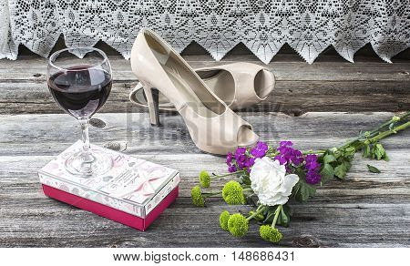 horizontal image of a pair of shoes lying on a wood floor beside a glass of wine and some flowers and a box of valentine chocolates.