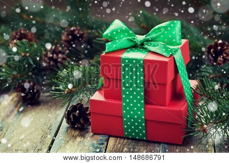 Red present box with bow, ribbon, decoration of fir tree and conifer cone with magic snow effect on wooden rustic board. Christmas or New Year background.