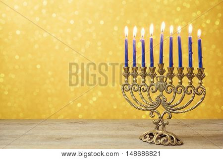 Jewish holiday Hanukkah background with vintage menorah over lights bokeh.