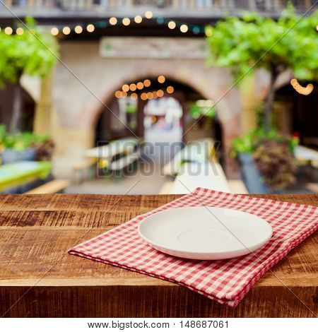 Empty plate on wooden rustic table with tablecloth over festive market bokeh background