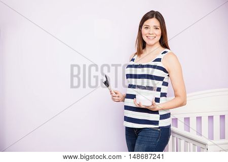 Pregnant Woman Decorating The Nursery