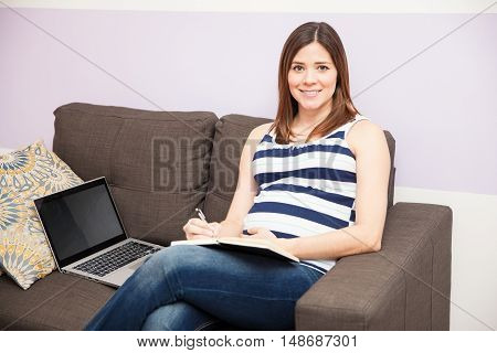 Pregnant Woman Taking Notes At Home