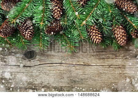 Christmas decoration of fir tree and conifer cone on textured wood background, magic snow effect, top view.