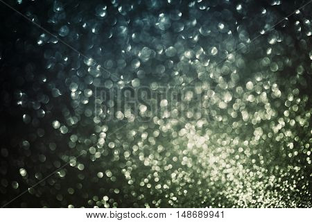 Glitter bokeh background, abstract texture of defocused lights. Vintage blue and gold color.