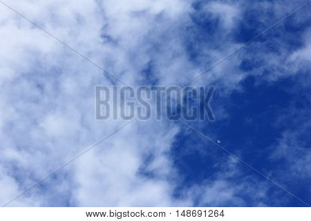 small plane silhouette in the clouds against the blue sky view from below / travel by plane