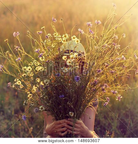 large bouquet of summer wildflowers behind which hidden a person in a hat / game hide and seek at sunset