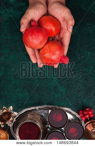 Man's hand with a pomegranate and pomegranate juice on textural background top view with copy space