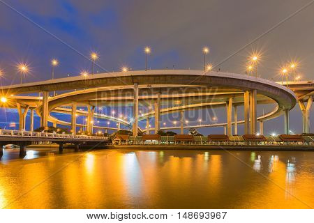 Night highway interchanged water front with twilight sky background
