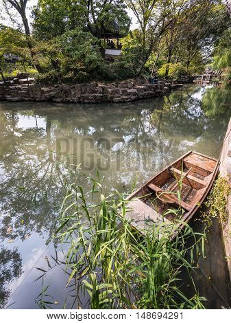 Suzhou China - October 232016: Small Chinese wooden boat with reflected trees in the Humble Administrator's Garden Suzhou China.