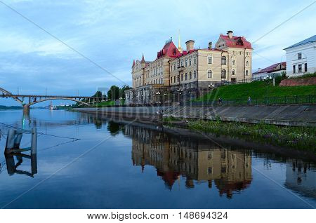 Building of former Grain Exchange on waterfront with reflection in water at night Rybinsk Russia