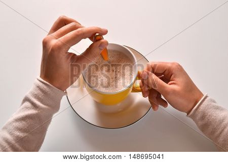 Hand holding a spoon with coffee cup and mixing.