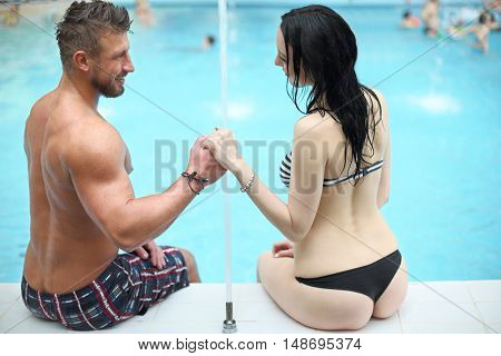 Tanned man and light-skinned woman in swimwear holding hands and looking at each other sitting by the pool, view from the back