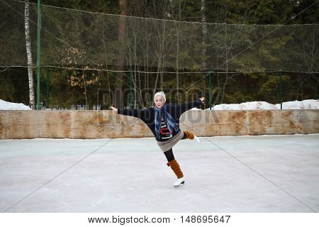 Young girl skating on one leg with arms outstretched to the sides on a skating rink