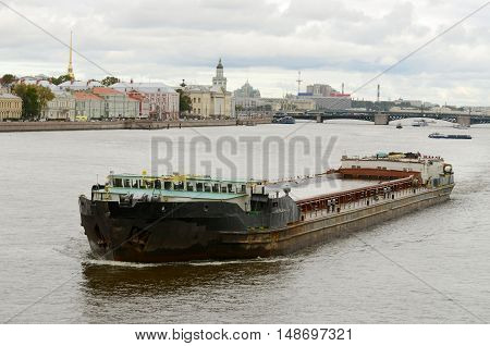 Big cargo ship floats on the river in the city.