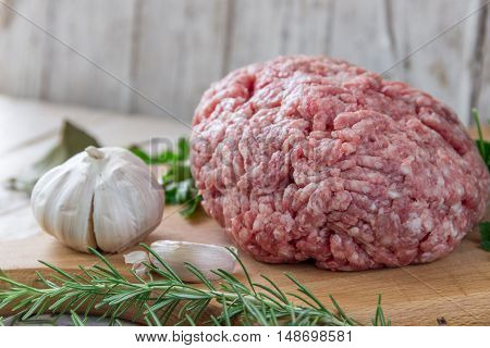 Raw ground beef meat steak cutlets with herbs and spices on white table or board for background. Healthy eating