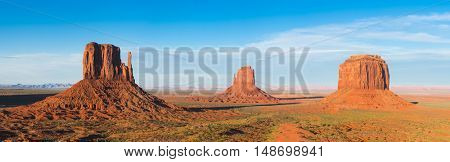 Beautiful dramatic sunset over the Mittens Buttes and Merrick Butte in Monument Valley. Utah, USA. Panoramic photo