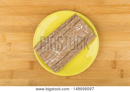 Crispbread In Yellow Glass Saucer On Bamboo Table