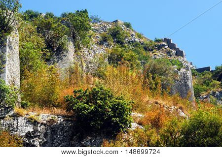 Detail of a mountain fortification system of Kotor (Montenegro), surrounded by autumn vegetation