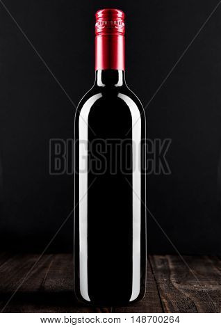 Bottle of red wine dark glass on wooden bacground red top