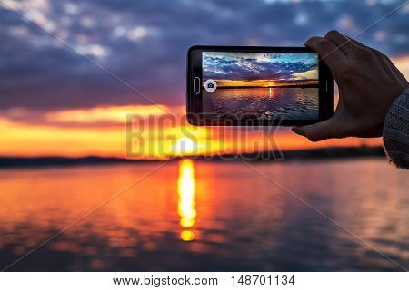 woman hands holding mobile phone at sunset.