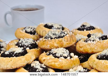 Homemade cakes with poppy seeds on a plate with a cup of coffee