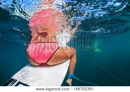 Back view of young girl in bikini. Surfer sit on surf board wait for ocean wave. Woman feet underwater photo. People in water sport adventure camp swimming extreme surfing on summer beach vacation