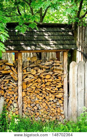 Fire wood under a canopy outdoor near the fence.
