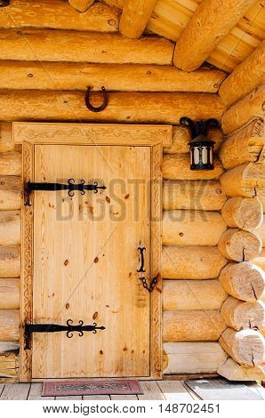 Doors with wrought iron hinges in the wooden house. In the historical park