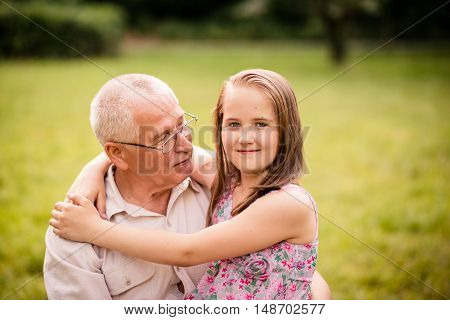 Smiling child hugging her happy grandfather - outdor in nature