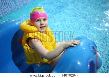 Little girl in a swimming hat and life jacket on a hill in the pool
