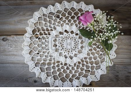 horizontal image of a vintage round white doily lying on an old rustic wood background with a pink rose lying on it with copy space.