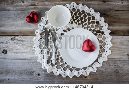 horizontal image of an overhead shot of an empty white plate and cup with a knife and fork sitting on a round white doily adorned with two red hearts on a rustic wood background.