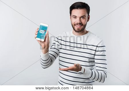 Just a message. Young handsome man smiling and demonstrating cellphone while standing against white background.