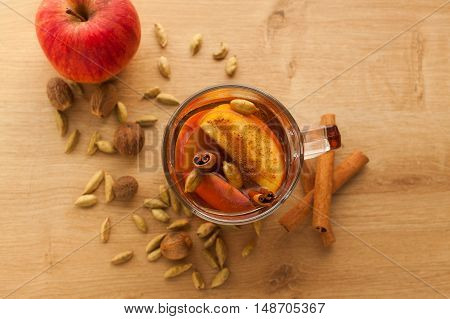 Closeup of hot tea with apple, cinnamon and cardamom. Autumn healthy drink to warm yourself in cold weather. Vitamin beverage with spices.