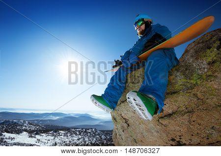 Snowboarder sitson the big stone on blue sky backdrop. Sheregesh, Siberia, Russia