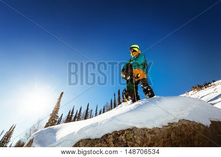 Snowboarder stands on the big rock keeps snowboard and looking far away. Sheregesh resort, Siberia, Russia