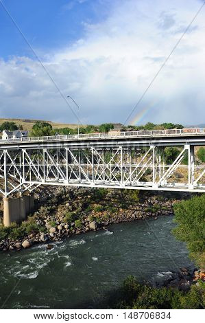 Gardner Montana is split by the Yellowstone River. Bridge spans river and rainbow form in storm clouds in distance.