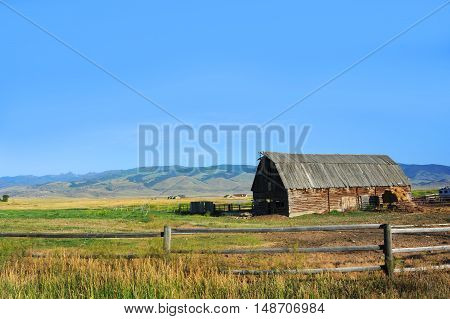 Rustic pole barn sits in a field in Happy Valley Montana. Wooden fence sets off coral. Roof of barn is wooden.